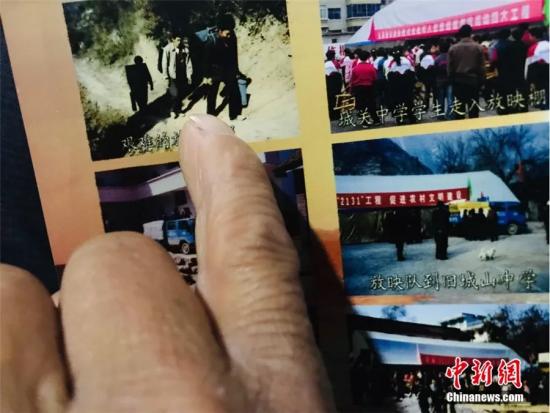图为尹凤民指着过去的照片。闫姣 摄
