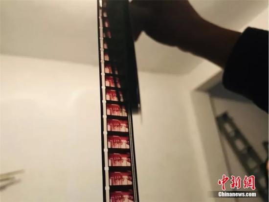 图为尹凤民展示旧胶片。闫姣 摄