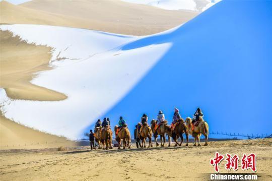图为11月15日,游客在雪后的甘肃敦煌鸣沙山月牙泉景区欣赏大漠雪景。 王斌银 摄