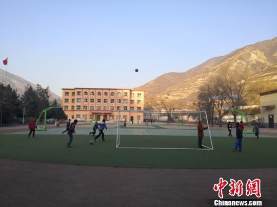 图为修葺一新的操场上,同学们踢足球。 杨娜 摄