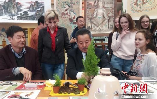 """图为何文华在""""中国甘肃民间艺术家赴俄罗斯专题交流展""""上现场制作瓷雕盆景。 受访者供图 摄"""
