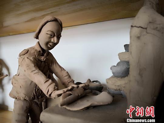 """如今,刘泉用手捏出的""""黄土情缘"""",已经被很多地方的农耕博物馆收藏,并且经常收到""""订单"""",让其泥塑黄土地农耕文明。 魏建军 摄"""