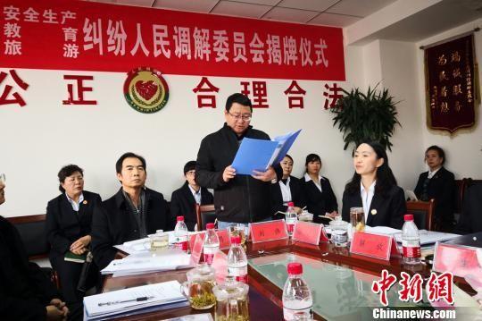 兰州市城关区司法局局长刘伟宣布对三个人民调解委准予登记的函。 高展 摄