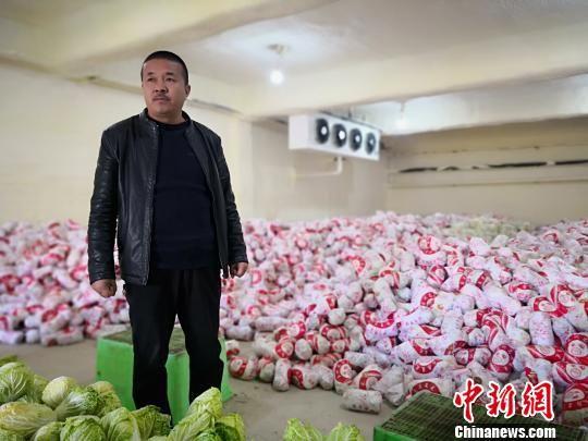 图为王建林介绍果蔬保鲜库及蔬菜销售情况。 魏建军 摄