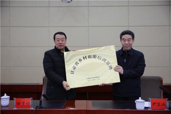 图为甘肃省文化和旅游厅副厅长田学功向永靖县委书记尹宝山授牌。