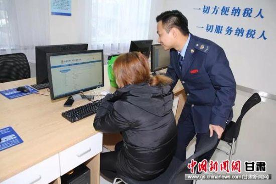 税务工作人员辅导纳税人网上办理涉税业务。