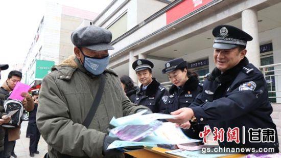 图为崆峒公安分局民警为民众发放110宣传日活动资料。