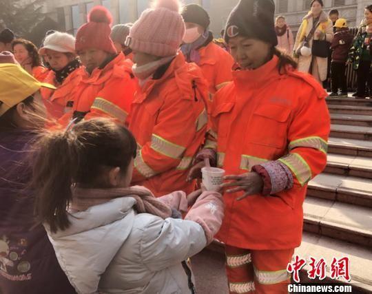 图为小志愿者为环卫工人送去腊八粥。 姜尧 摄