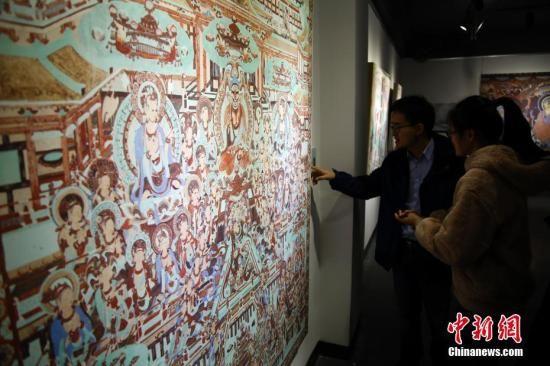 资料图:精美的敦煌壁画吸引参观者。 汤彦俊 摄