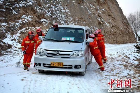 图为雪后山路打滑,护林员推着宣传森林防火的宣传车前进。 郭红 摄