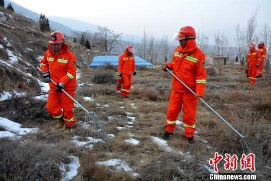 图为护林员拿着铁扫帚巡山护林,做好冬季防火工作。 郭红 摄