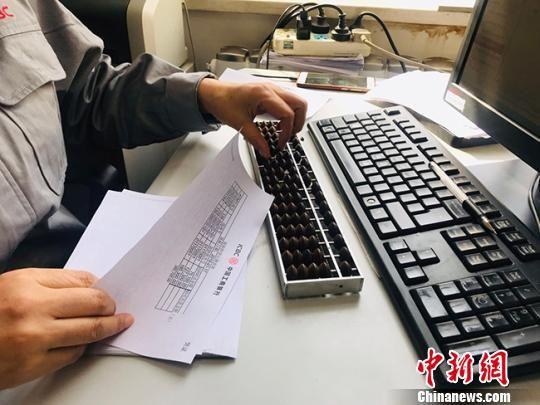 图为记账员徐玉兰用算盘核查凭证数字。 艾庆龙 摄