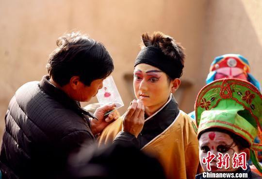 图为秦安县社火表演,正绘制脸谱。 师永红 摄