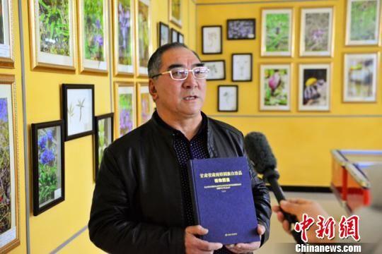 图为安国庆和他主编完成的《甘肃省肃南裕固族自治县植物图鉴》。 钟欣 摄
