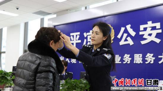 图为民警为办证拍照群众整理头发。