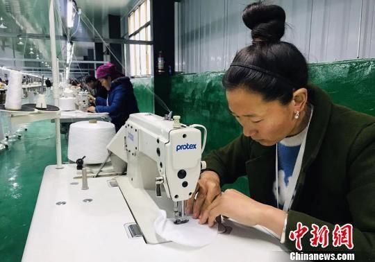 紧挨着坪垭藏族乡腰道村易地搬迁点的扶贫车间内,村民们在缝制宾馆用品。 艾庆龙 摄