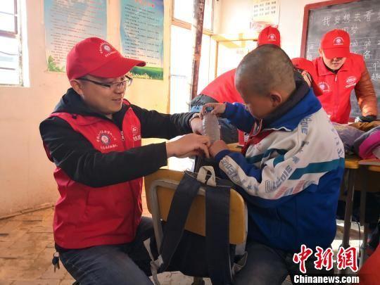 樊恒东(左)给甘肃榆中县北山的魏家台教学点小学生送学习用品。 许岗 摄