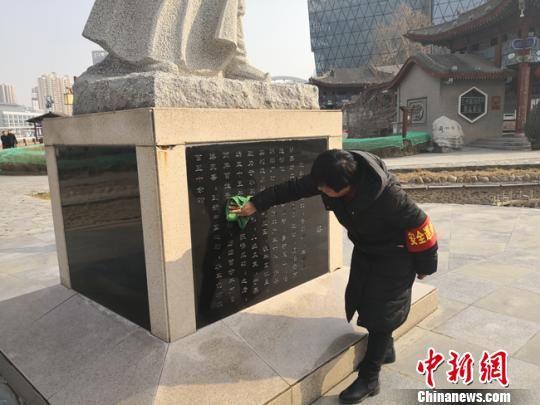 图为水车博览园工作人员郝燕擦拭石碑。 杨娜 摄