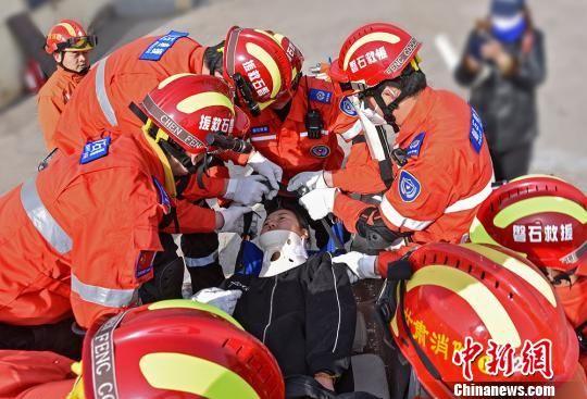 图为救援队员将被困者移出车体。 师永红 摄
