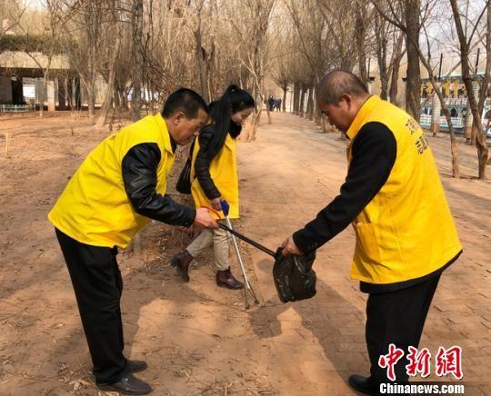 图为志愿者捡拾黄河岸边小游园内垃圾。 姜尧 摄