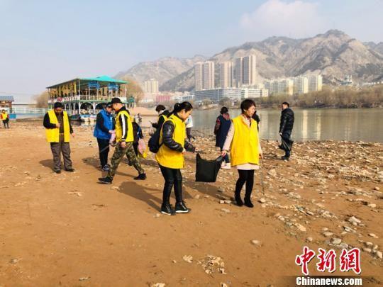 图为志愿者沿黄河捡拾垃圾。 姜尧 摄
