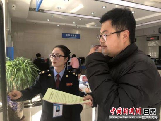 分局干部王苗向纳税人宣传税收政策。