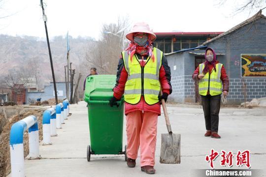图为临夏市折桥镇大庄村村级环卫工崔小红(左)清扫道路。 马孝 摄