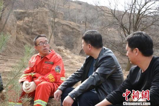 图为马雪峰正在与同事交流护林经验。 魏丽 摄