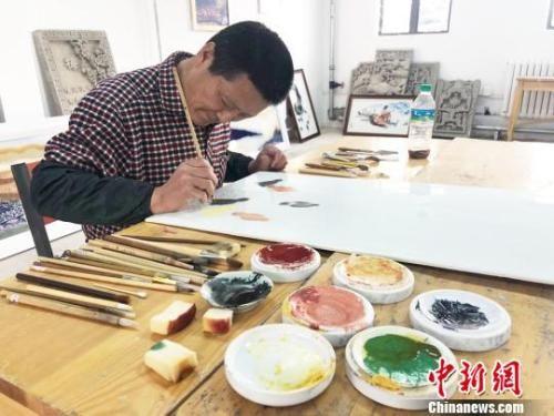 近日,甘肃瓷板画艺人王清路在工作室里进行创作。 徐雪 摄