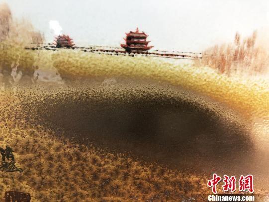 """如今王清路凭借出色的技艺成为""""中国传统工艺大师""""""""甘肃省工艺美术大师"""",他将粗犷豪放的西北风光融入进瓷板画的创作之中,题材涉及敦煌莫高窟、月牙泉、天下第一雄关嘉峪关、祁连山等。 徐雪 摄"""
