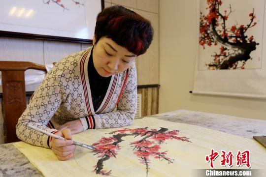 业余时间,佟红梅爱好画梅。 高展 摄