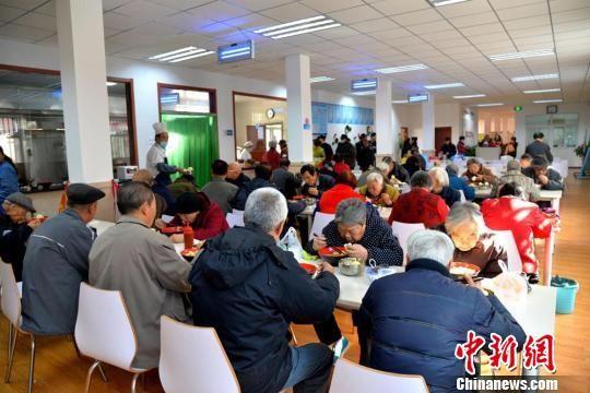 图为老人们正在兰州市西固区幸福社区老年人日间照料中心食堂就餐。(资料图)  郭炯 摄