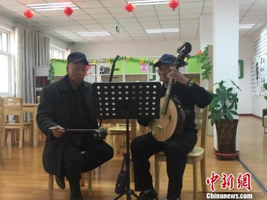 2017年3月23日,兰州市西固区幸福社区老年人日间照料中心,老人们正在活动室,练习演奏。(资料图)  杜萍 摄