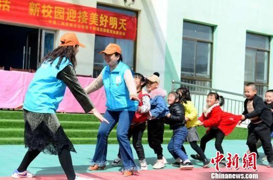 图为志愿者们和树屏镇镇中心幼儿园的孩子们做游戏。 崔琳 摄