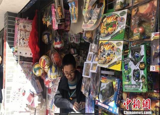 图为3月19日,小学生在校园周边便利店挑选商品。 史静静 摄