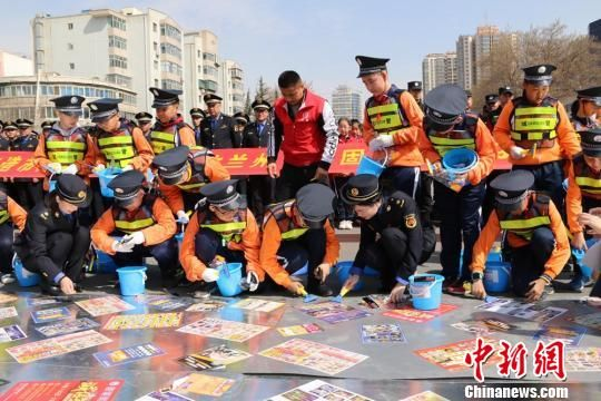 """图为小学生和城管队员一起铲除城市""""牛皮癣""""。 王能学 摄"""