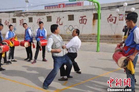 """图为老师向学生示范凉州""""攻鼓子""""舞步和阵法。 钟欣 摄"""