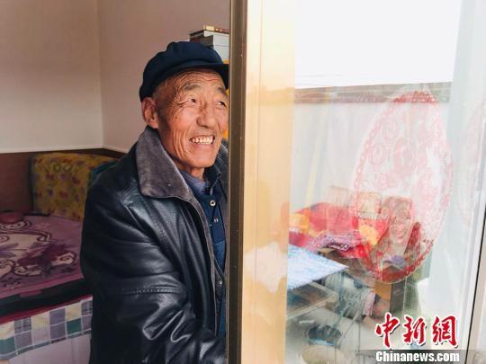 67岁的村民金富贵擦拭着新房子的玻璃。 艾庆龙 摄