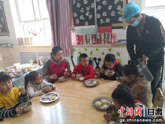 图为老师与小朋友一起用餐。