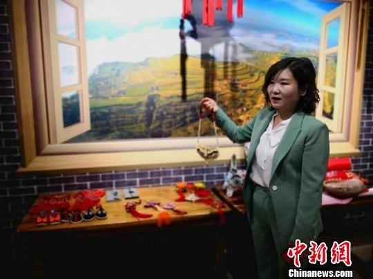 """图为甘肃酒泉""""创业妹""""邓世贤介绍农村妇女们的手工艺品。 闫姣 摄"""