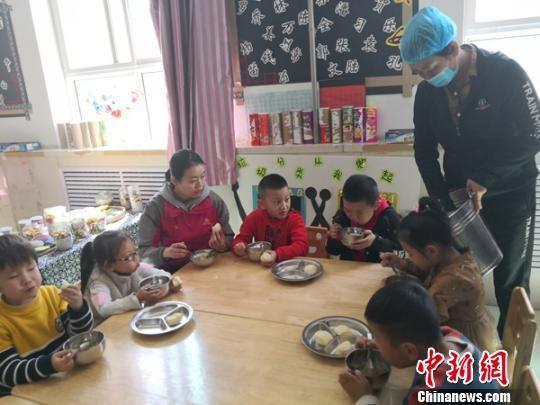 图为老师与小朋友一起用餐。 杨娜 摄
