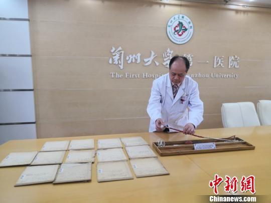 4月10日,兰州大学第一医院院长李汛向记者介绍由杨英福教授从美国带回的中国首台沃尔夫・辛德(Wolf.Schindler)半屈式金属胃镜的用法。 杨娜 摄
