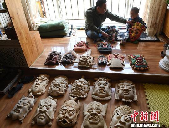 甘肃民间艺人马正德展示制作的傩面具。 杨艳敏 摄
