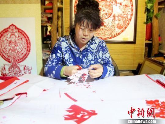图为敦煌剪纸传承人何克风在月牙泉小镇的剪纸店里认真创作。(资料图) 田明君 摄