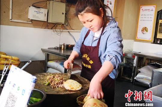 图为张莎在月牙泉小镇做陕西潼关肉夹馍。(资料图) 南如卓玛 摄