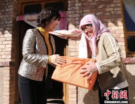 """甘肃省妇女儿童基金会负责人周华(左)为定西市渭源县大安乡单亲母亲们送去了""""爱心包""""。 闫姣 摄"""