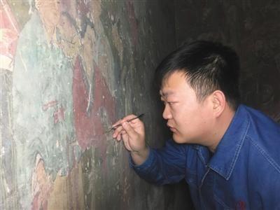 李晓洋在修复壁画。图片来源:新京报