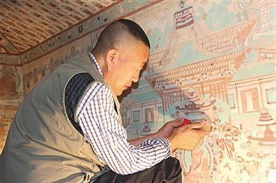 李波在修复壁画。图片来源:新京报