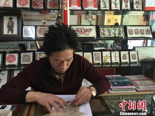甘肃皮影雕刻艺人赵德才伏案按照纸质模板雕刻皮影。 刘薛梅 摄