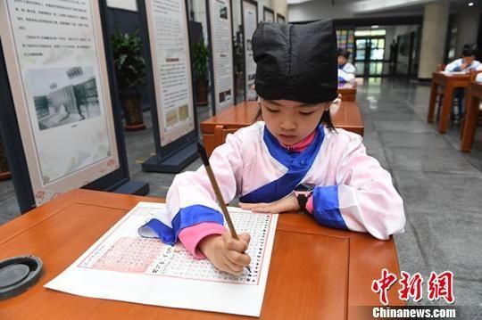 图为小学生抄写古籍经文。 杨艳敏 摄